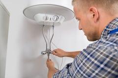 Fontanero Repairing Electric Boiler fotografía de archivo libre de regalías