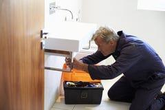 Fontanero Working On Sink en cuarto de baño Foto de archivo libre de regalías