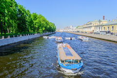The Fontanka river in Saint Petersburg. Summer cityscape near the Summer Garden in St. Petersburg. On the river Fontanka pleasure boats with tourists and jet Royalty Free Stock Image