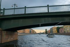 Fontanka River under the Krasnoarmeysky bridge. RUSSIA, SAINT PETERSBURG - AUGUST 18, 2017: A promenade excursion boat with tourists goes along the Fontanka Royalty Free Stock Photo