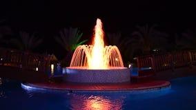 Fontanna w pływackim basenie przy luksusowym hotelem w nocy iluminaci