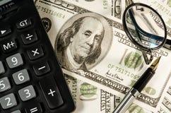 Fontanny pióra kalkulator na 100 dolarach i szkła Fotografia Stock
