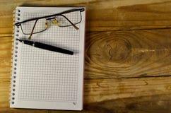 Fontanny pióro, szkła i notatnik na drewnianym stole, Obrazy Stock