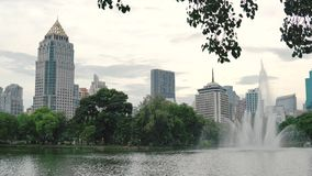 Fonte alta bonita na superfície do lago no parque da cidade no fundo do centro das construções Pulverizador da fonte que cai d video estoque