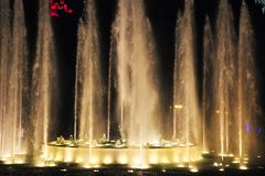 A fonte bonita dá a mostra clara que espirra a água dentro à noite escura imagens de stock