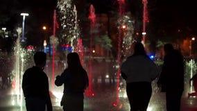 Fonte colorida da dança na noite metragem do close up do Lento-movimento dos jatos da água em um fundo escuro unrecognizable filme