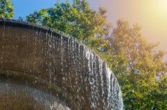 A fonte com água que cai no fundo da árvore e do Sun fotos de stock