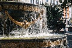 Fonte com com gotas douradas do estuque e da água do gelo Imagem de Stock
