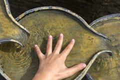 Fonte com um child& x27; mão de s Imagem de Stock