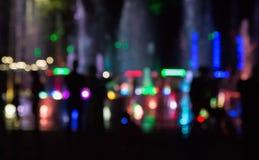A fonte da cidade com iluminação da cor na noite fora de foco imagem de stock royalty free