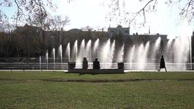 Fonte da cidade footage Povos que andam no parque Fonte no parque da cidade no dia de verão quente Córrego da água, gotas e filme