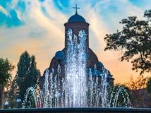 A fonte de água cabe no contorno da igreja fotografia de stock royalty free