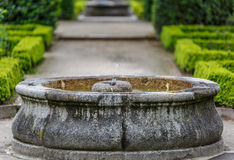 Fonte de água de pedra no meio de um jardim bonito Imagem de Stock Royalty Free