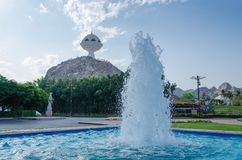 A fonte de água e o Riyam estacionam o monumento contra o céu azul Fotos de Stock