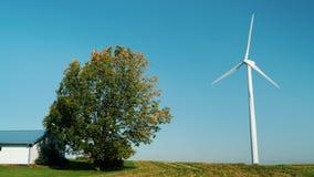 Fonte de alimentação independente de uma casa ou de uma exploração agrícola O gerador de vento perto da construção, uma árvore es filme