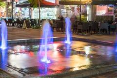 Fonte de incandescência perto do café do verão da noite em Pomorie, Bulgária Fotografia de Stock Royalty Free