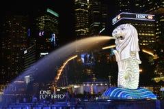 A fonte de Merlion jorra a água na frente do um Fullerton Fotografia de Stock Royalty Free
