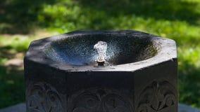 Fonte de pedra com close-up da água potável, foco seletivo, DOF raso imagem de stock