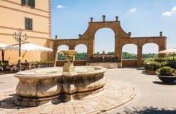 Fonte e arcos antigos no quadrado de Repubblica, em Pitigliano, Fotografia de Stock
