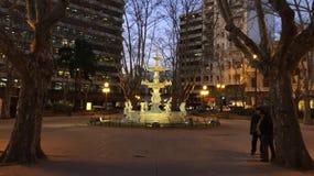Fonte em um quadrado quadro por árvores na noite Foto de Stock Royalty Free