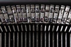 Fonte em uma máquina de escrever Selos do metal para imprimir letras em uma folha branca fotos de stock