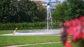 Fonte grande do verão perto da fonte senta uma menina da criança, olhando a água Dia quente do verão filme