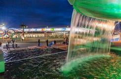 A fonte iluminada da cascata da cachoeira no parque olímpico encanta com seu jogo bonito da água e da luz Imagem de Stock