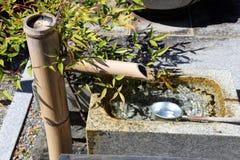 Fonte japonesa velha com uma tubulação de bambu fotos de stock