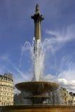 Fonte no quadrado de Trafalgar com a coluna dos nelsons no fundo Imagens de Stock