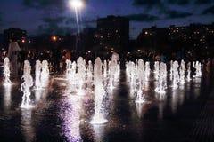 A fonte seca bonita com branco iluminou jatos na noite escura foto de stock royalty free