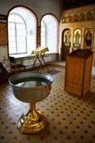 Fonte tipografica battesimale di acqua santa vicino all'altare Fotografia Stock