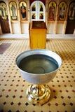 Fonte tipografica battesimale vicino all'altare in chiesa cristiana Immagini Stock