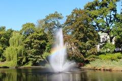 Fontein in het meer met regenboog Stock Afbeeldingen