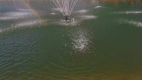 Fontein in het midden van het meer en de regenboog stock footage