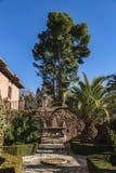 Fontein met beeldhouwwerken in weinig geopend terras in Alhambra Garden stock foto's