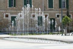 Fontein op stadsvierkant in daglicht stock afbeeldingen
