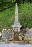 Fontein van de eeuwen de oude die steen in vorm van obelisk met het runnen van zoet water gedeeltelijk in nat omringd mos met ste royalty-vrije stock foto