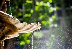 Fonteindetail met het laten vallen van water van het en het zitten van de langsligger Stock Fotografie