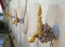 Fonteinen van de metaal de gele tapkraan op een rij in oude traditionele stad stock foto's