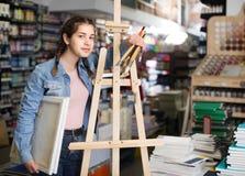 Fontes adolescentes da terra arrendada da menina para pintar nas mãos no departme da arte imagem de stock royalty free
