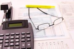 Fontes da preparação do imposto, vidros de leitura e formulários de imposto fotografia de stock