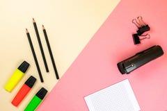 Fontes de escola, caderno e marcadores coloridos no fundo cor-de-rosa e bege pastel foto de stock