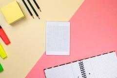 Fontes de escola, caderno e marcadores coloridos no fundo cor-de-rosa e bege pastel foto de stock royalty free