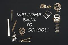 Fontes de escola colocadas no fundo preto com boa vinda do texto de volta à escola fotografia de stock royalty free