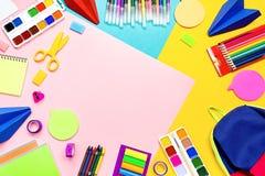 Fontes de escola com artigos de papelaria coloridos Marcadores, lápis, cadernos, trouxa no fundo multicolorido, espaço da cópia foto de stock