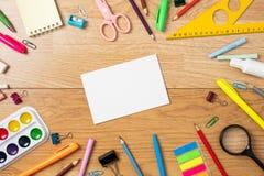 Fontes de escola na tabela de madeira, no fundo com o quadro feito dos artigos de papelaria e no cartão de papel vazio no centro  foto de stock