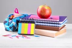Fontes de escola que incluem uma caixa de lápis, livros e cadernos em um fundo de madeira branco fotografia de stock royalty free
