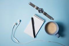 Fontes de escritório Vista superior no caderno, na pena, no fones de ouvido, no portátil e na xícara de café abertos no azul Imagem de Stock Royalty Free
