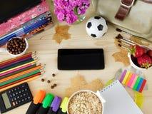 Fontes dos artigos de papelaria e um smartphone com uma tela vazia no meio foto de stock royalty free
