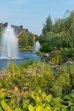 Fontes em um lago cercado por árvores e por flores verdes, na perspectiva de uma casa de campo de madeira enorme e de um azul Fotos de Stock Royalty Free
